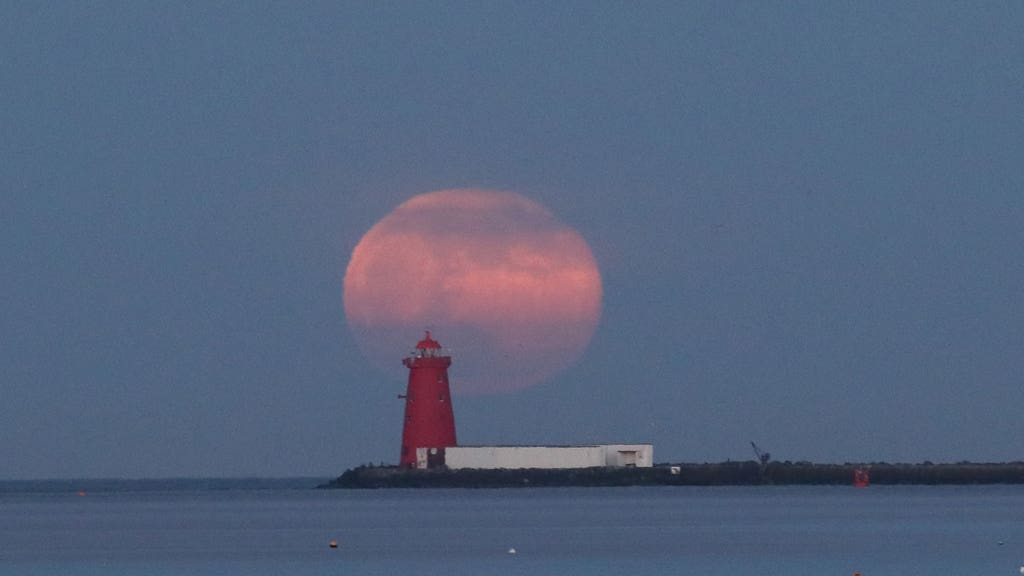 Pink supermoon over lighthouse